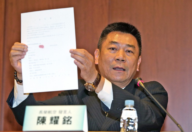 EVA Airways Corp public relations vice president David Chen holds up letters of authorization from flight attendants who wish to return to work during a news conference in Taipei yesterday. Photo: CNA