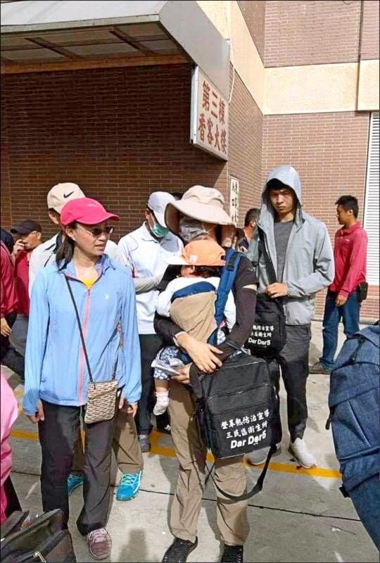 三民衛生所廖姓女員工被迫背著一歲幼兒加班,為登革熱防疫奮戰。(記者陳文嬋翻攝)