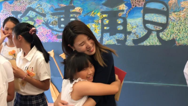 日本女大生椿原世梨奈(黑衣者)今天出席宜蘭縣岳明國小畢典,與小朋友熱情擁抱。(記者江志雄翻攝)
