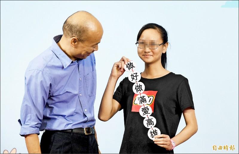 中華藝校李姓畢業生與市長韓國瑜合影時拿出「做好做滿愛高雄」字聯。(記者張忠義攝)