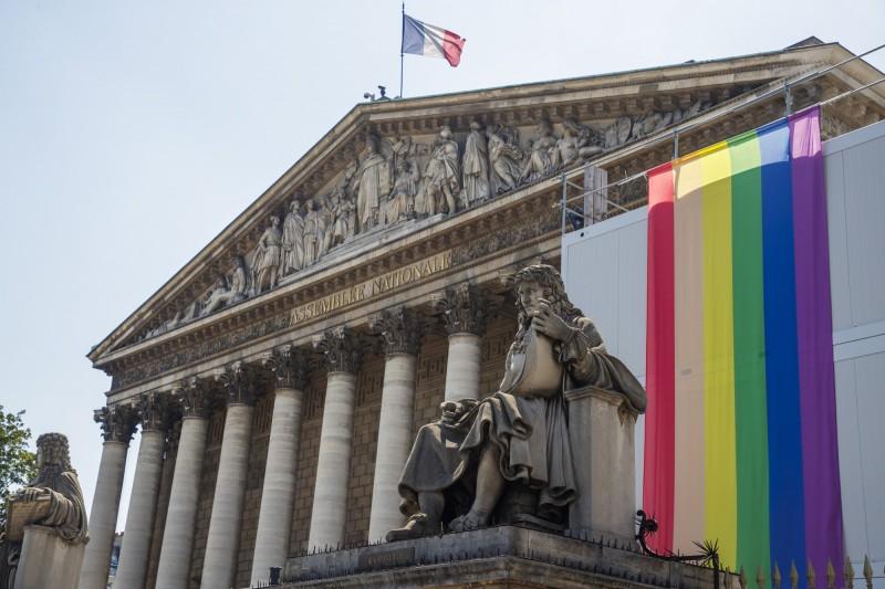 法國巴黎同志遊行將在本月29日舉行,預估會有50萬人參加,希望能減少外界對同性戀者的排斥心態,也鼓勵LGBT群體能夠更有自信的展現自我。圖為去年巴黎同志遊行期間,展示彩虹旗的法國下議院。(歐新社)