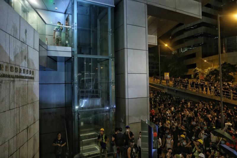 期間一名警員疑似混入民眾中,煽動民眾衝進總部大樓,這名港警的身分曝光後,遭到民眾包圍,最後逃進警察總部內。(歐新社)