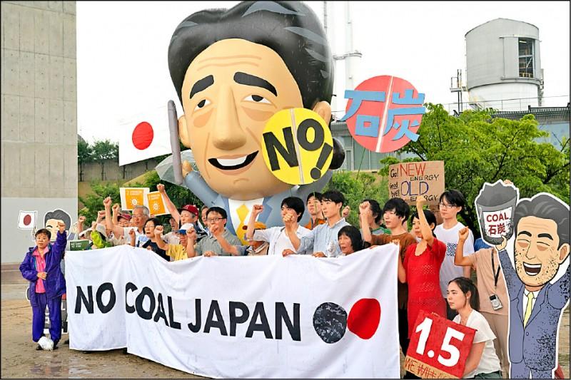 二十國集團(G20)峰會今天召開,全球氣候變遷和環境議題乃成員國間的磋商重點。圖為日本環保人士與地方居民二十七日在神戶,以一個日本首相安倍晉三造型的充氣娃娃,表達希望日本勿再使用煤炭進行火力發電,以減少溫室氣體排放量的訴求。(美聯社)