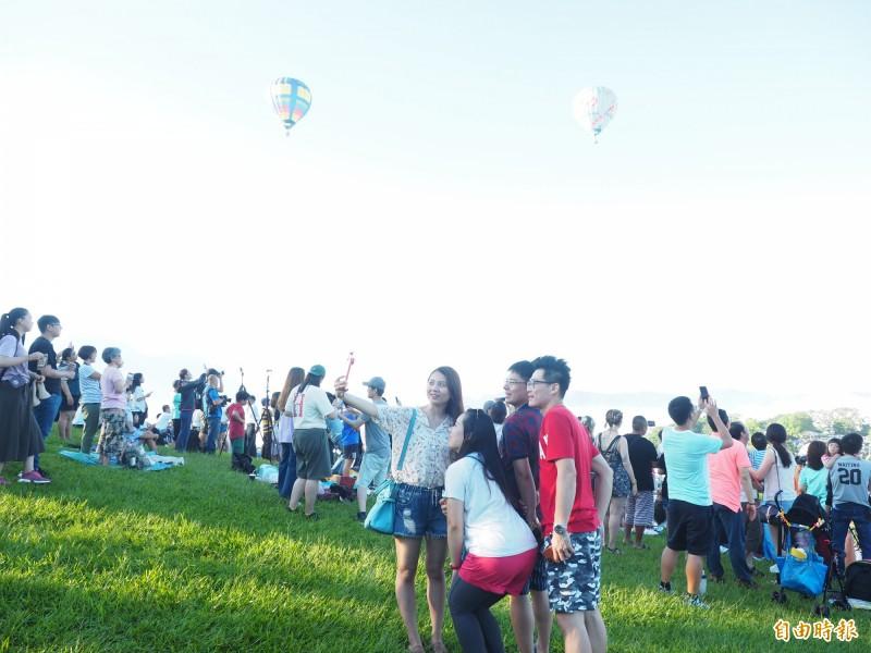 民眾見熱氣球自由飛往觀眾區,立刻拿起相機拍照。(記者王秀亭攝)