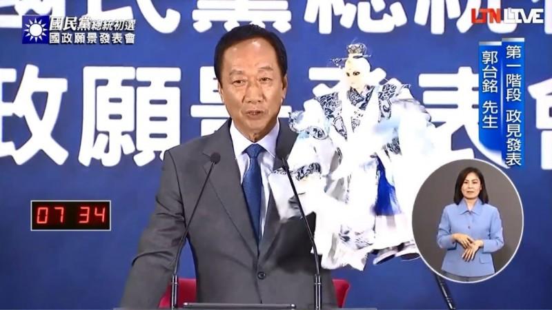國民黨初選參選人郭台銘在今天的國政願景電視發表會上,拿出素還真的布袋戲偶高呼「素還真來囉!」。(圖擷取自本報直播)