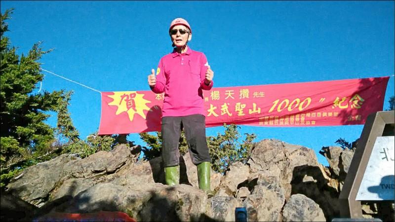71歲楊天攢完成攻頂北大武山1千次,當天他穿著招牌紅色膠盔、雨鞋,山友為他製作紅布條慶賀。(記者洪臣宏翻攝)
