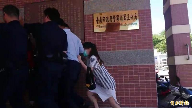 施姓新手媽在警方維護下,快步奔進分局。(記者王捷攝)