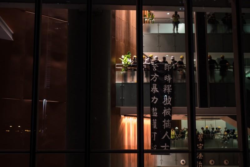 闖入立法會大樓的示威者,掛上「即時釋放被捕人士,警方暴力濫權可恥」的布條。(彭博)