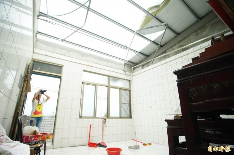 林邊鎮安村該戶民居的整片鐵皮屋頂全被吹飛,連室內冰箱都被捲出到室外。(記者陳彥廷攝)