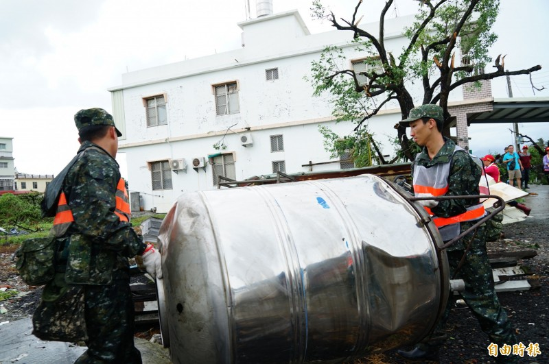 國軍冒雨將各式雜物清出。(記者陳彥廷攝)