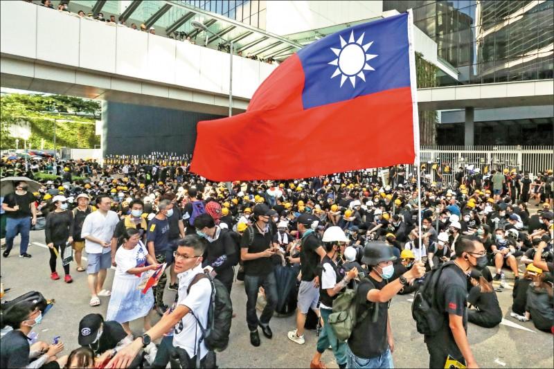 一名示威者在香港立法會外揮舞中華民國國旗。(歐新社)