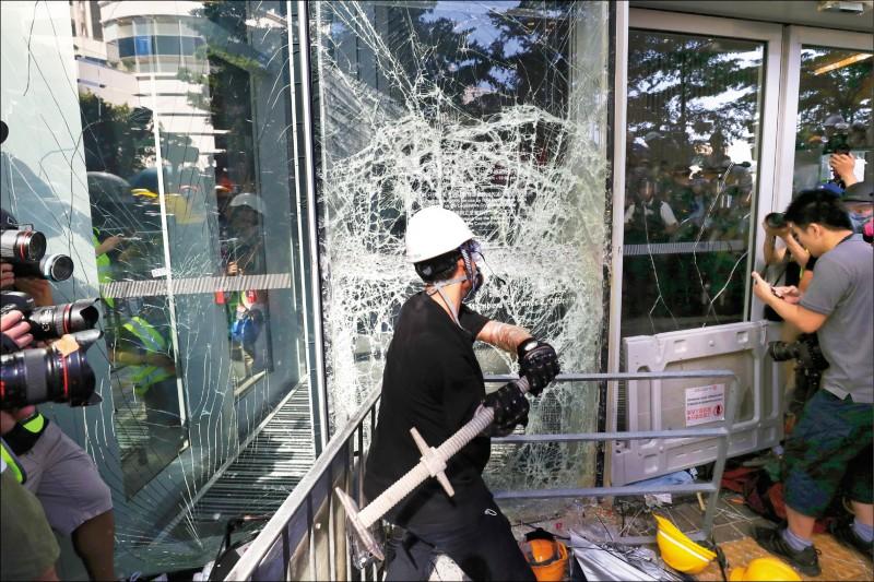 年輕示威者一日包圍香港立法會大樓,以鐵條敲打大樓玻璃門,企圖衝入立法會。(歐新社)