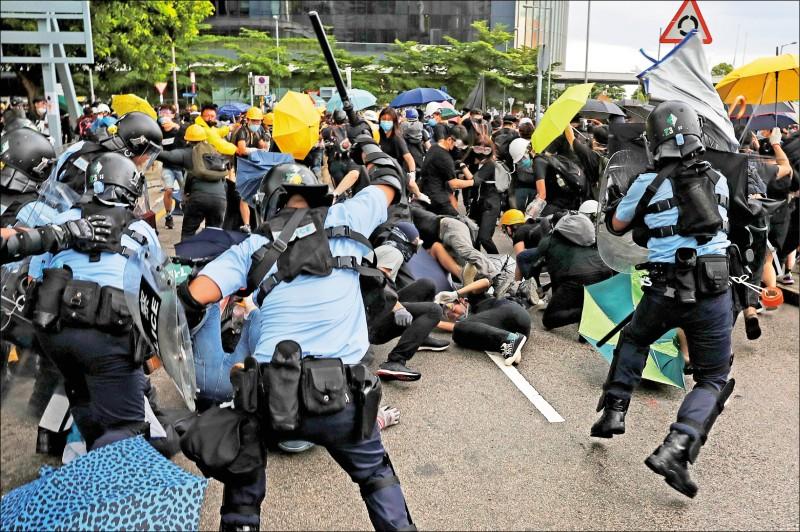 參與香港七一大遊行的民眾手持雨傘,與鎮暴警察對峙。(美聯社)
