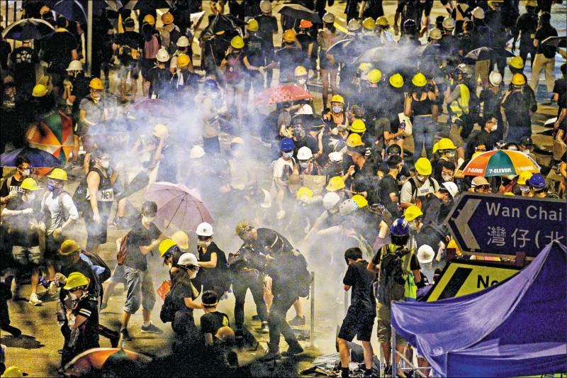 香港警方一日午夜過後展開清場,發射催淚彈,驅散金鐘政府總部、立法會外的抗爭群眾。(法新社)