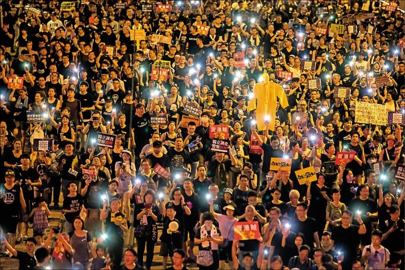參與香港七一大遊行的民眾,高舉手機形成一片燈海。(彭博)