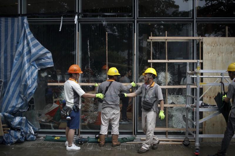 工人檢視遭抗議者破壞的香港立法會大樓玻璃門。(美聯社)