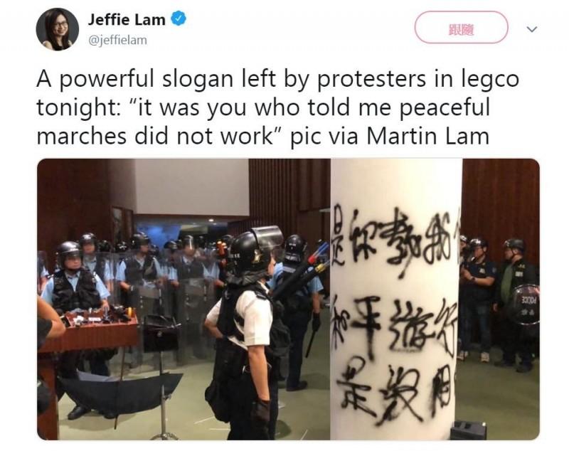 香港《南華早報》記者PO出照片,一名員警看著示威者以噴漆留在立法會內的標語,「是你教我們和平遊行是沒用的」,畫面令人震撼。(擷取自Twitter@jeffielam)