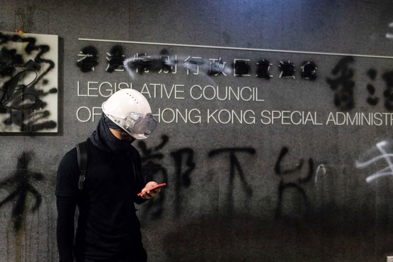 香港建制派議員認為,應該研擬反蒙面法,讓示威者以真面目示眾。圖為1名站在香港立法會大樓前的示威者。(彭博)