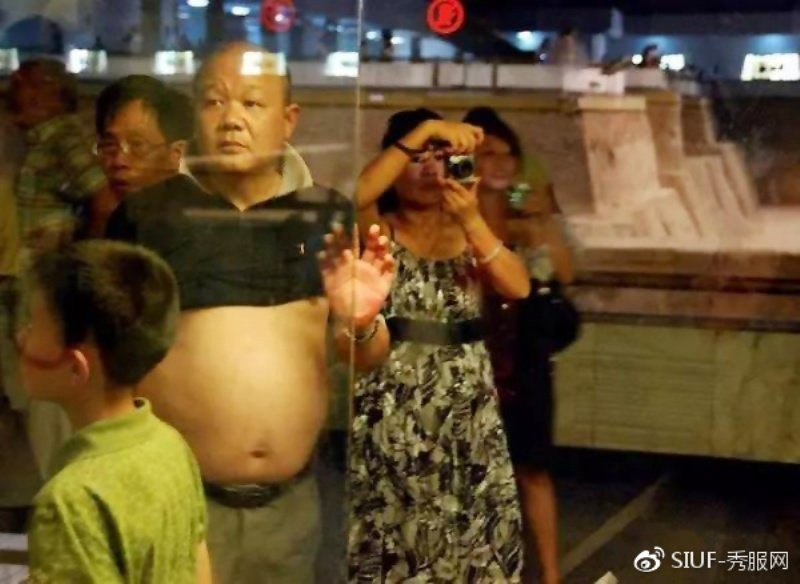 酷熱難耐的夏天是中國「膀爺」頻繁出沒的季節,這種撩起上衣、露出肚皮的穿法,被外國戲稱為「北京比基尼」。(取自微博)