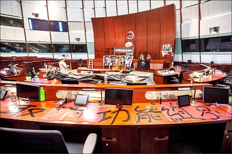 示威者在立法會會議廳桌上塗鴉,要求取消非由民主直選產生的功能組別議員。(彭博)