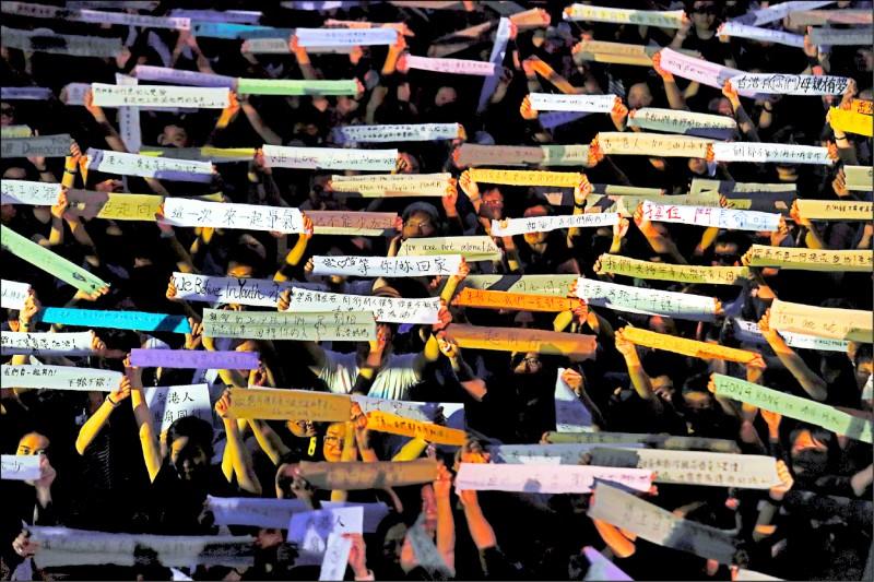 近八千名香港母親,五日晚間在港島中環遮打花園參與「生命與玻璃:香港人的選擇」集會,現場不少港媽在布條上寫下打氣字句,力挺反送中的香港年輕人。(美聯社)