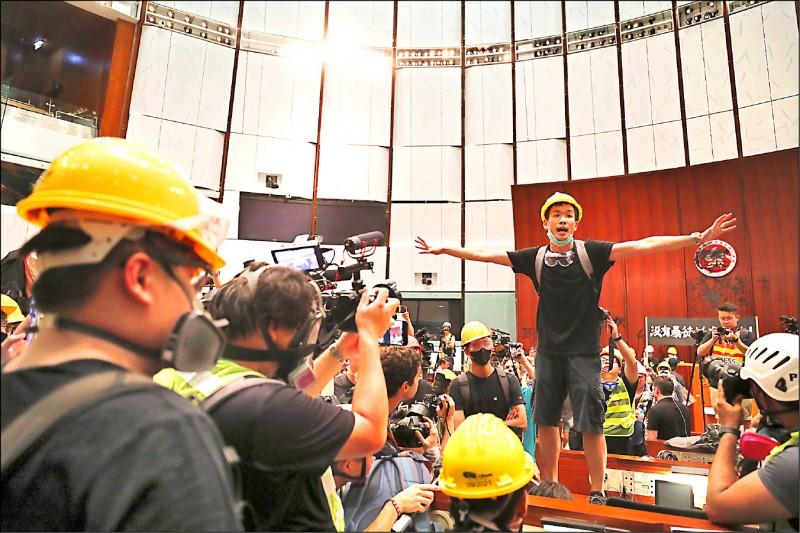 香港一日的佔領立法會行動中,示威者梁繼平摘下口罩、站在會議廳桌上,宣讀該次行動的訴求。(歐新社)
