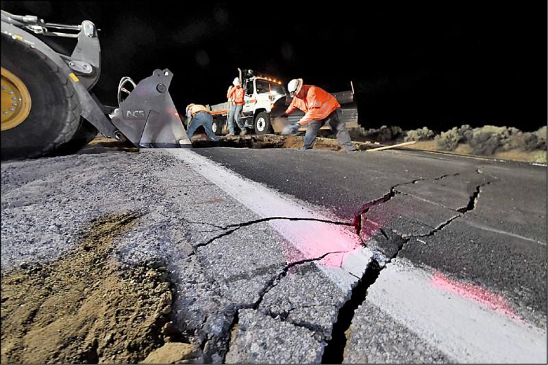 工人忙著修補地震所造成的路面龜裂。(法新社)