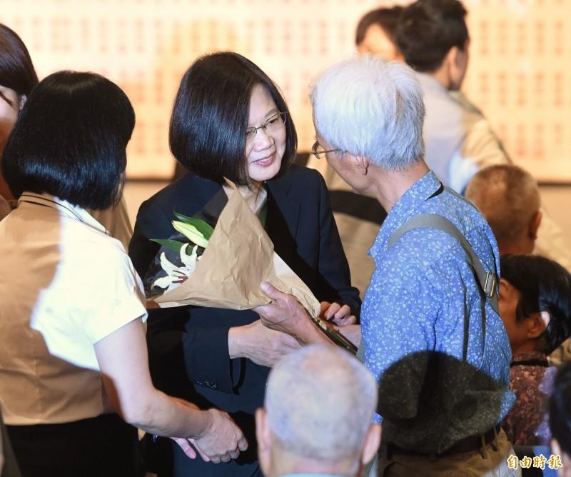 總統蔡英文7日出席「平復司法不法之第三、四波有罪判決撤銷公告儀式」,主持儀式後,一一獻花給獲平反的民眾。(記者方賓照攝)