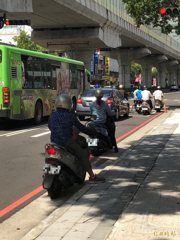 夏天天氣熱,常見騎士停等紅燈時會在停止線前的路邊陰涼處躲太陽。(記者許國楨攝)
