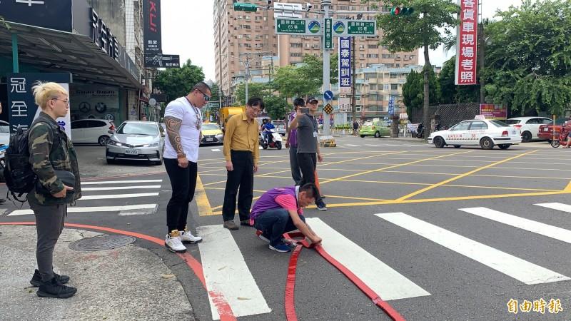網路紅人「館長」陳之漢和桃園市議員詹江村一起站在服務處門口燃放鞭炮。(記者陳恩惠攝)
