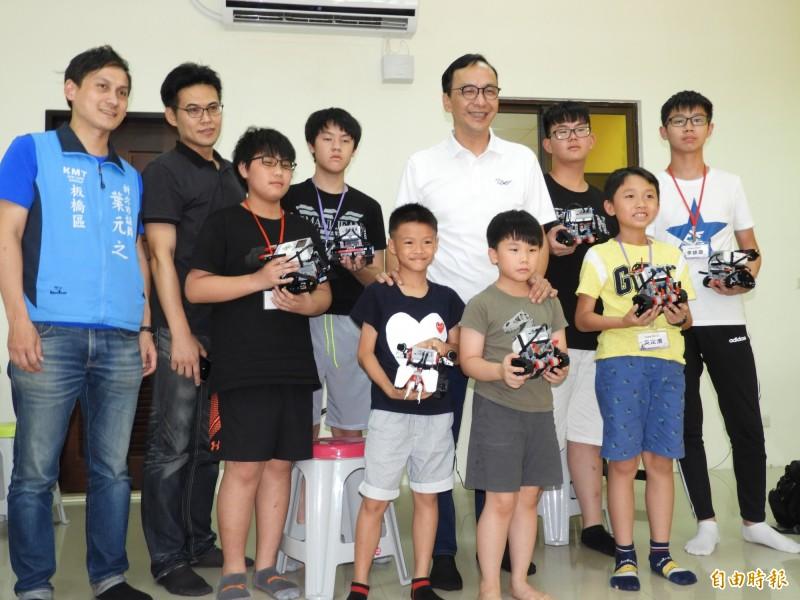 前新北市長朱立倫今天參訪板橋區「光點創意樂高機器人創客中心」,與學童們合照。(記者賴筱桐攝)