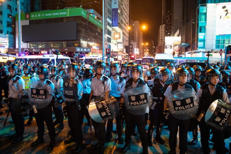九龍《反送中》大遊行,警方築人牆阻遊行前進。(彭博)