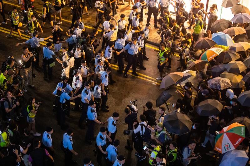 九龍《反送中》大遊行,港警人牆與民眾傘牆對峙。(彭博)