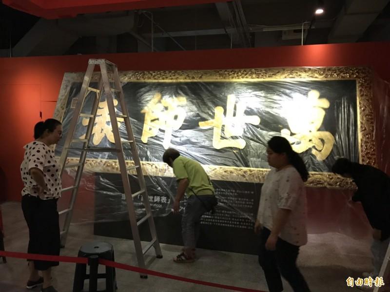 因應登革熱化學防治作業,鄭成功文物館人員為正在展出的台南孔廟清代御匾穿上「雨衣」。(記者劉婉君攝)