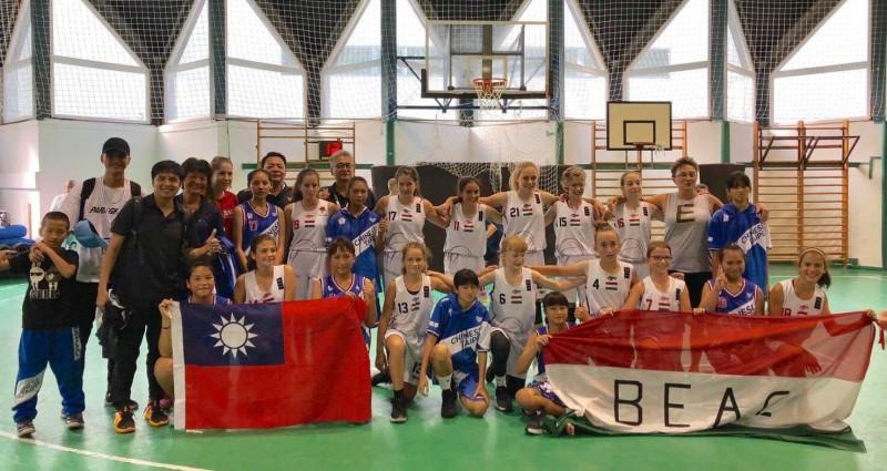 南澳國小女子籃球隊(左)持我國國旗,與外國球隊合影留念。(記者江志雄翻攝)