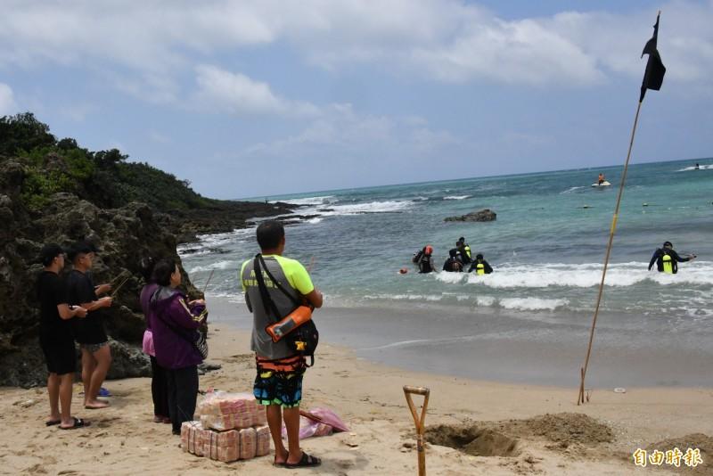 傷心的家屬及同行友人,在當地民眾協助下,在海邊插起黑旗焚香希望孩子快點回來。(記者蔡宗憲攝)