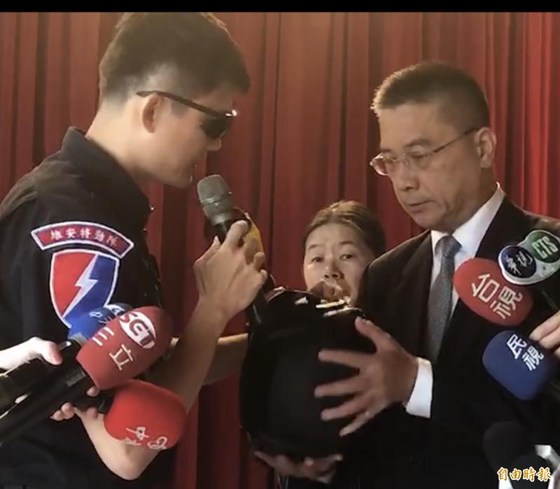 許員拿著防彈頭盔向徐國勇說明經過。(記者許國楨攝)