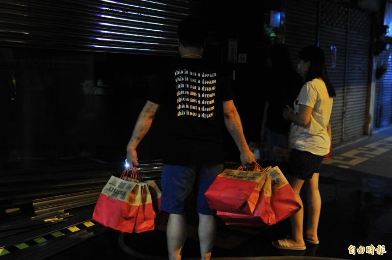 員工從火災現場拿出一袋袋麵包。(記者王捷攝)