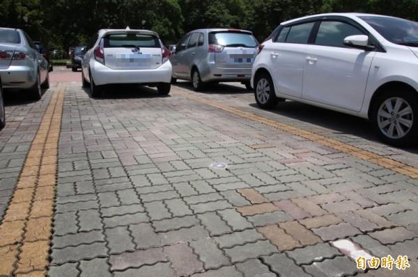 新竹縣政府前廣場等處共3235格的停車格,佈設有如圖地面上圓形的電磁感應器(地磁),8月以後就能透過這個地磁,搭配免費、遠傳的LINE@,智慧尋找車位停車。(記者黃美珠攝)