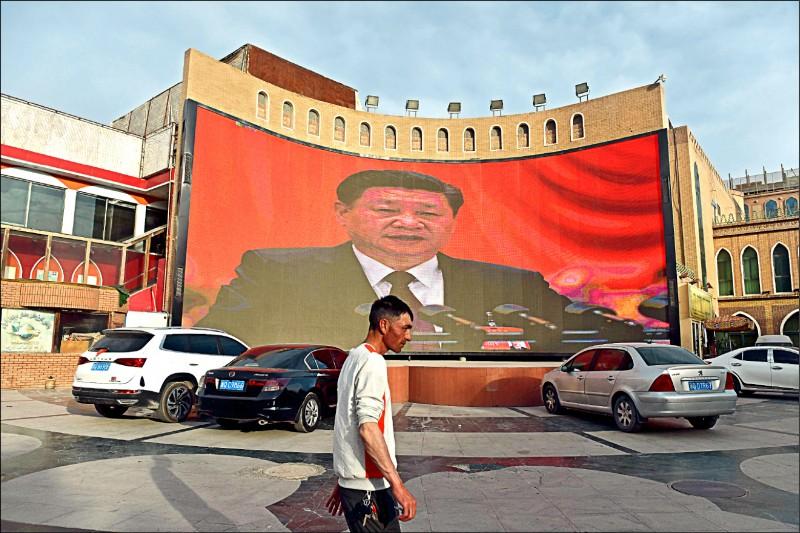 英國、日本等二十二個國家的駐聯合國大使發表聯名公開信,譴責中國監禁新疆維吾爾族和其他少數族裔,力促北京停止這種違反人權的做法。圖為新疆喀什市區一面大螢幕播出中國國家主席習近平的影像。 (法新社檔案照)
