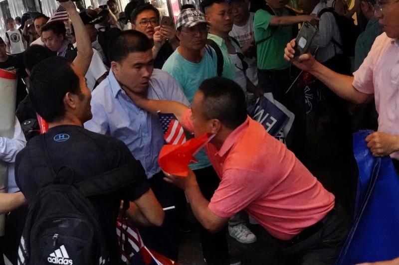 兩派人馬隔街互嗆,演變成激烈衝突、大打出手,雙方多人受傷,最後1人被逮補、1人送醫。(路透)