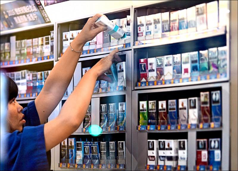 圖為超商店員為架上菸品補貨。(中央社資料照)