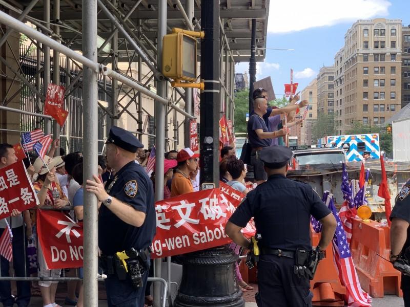 有數十名中國僑民聚集蔡下塌飯店對面人行道,播放中華人民共和國國歌。(中央社)