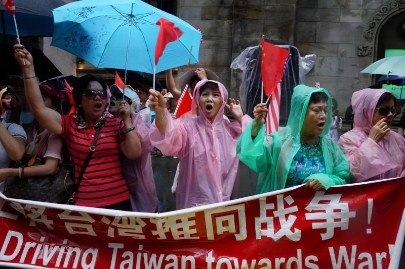 中國僑民在蔡總統下榻飯店外揮舞五星旗。(路透)