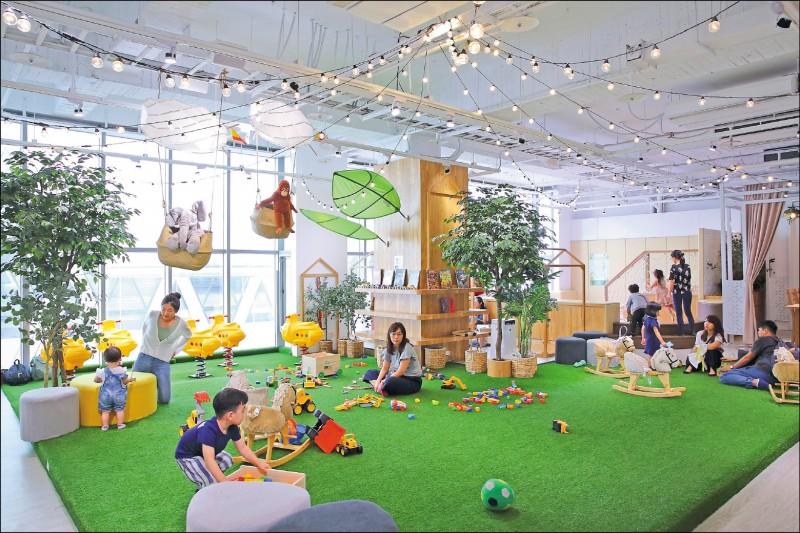 餐廳2樓的孩童遊戲區,以公園綠地及吊掛式燈泡營造野餐氛圍,小朋友可在寬敞的人工綠地上玩玩具、騎木馬等。(記者李惠洲/攝影)