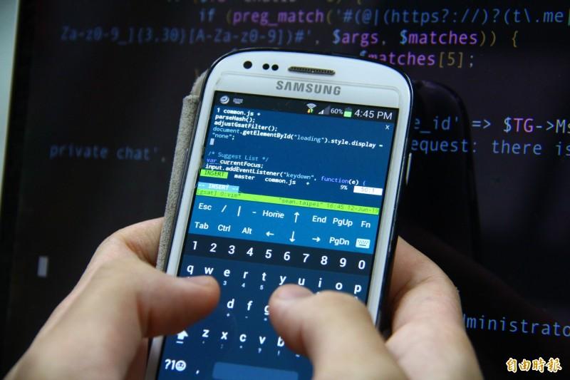 他笑著說國中只能用手機寫程式,雖然字體小但看久了也習慣。(記者邱書昱攝)