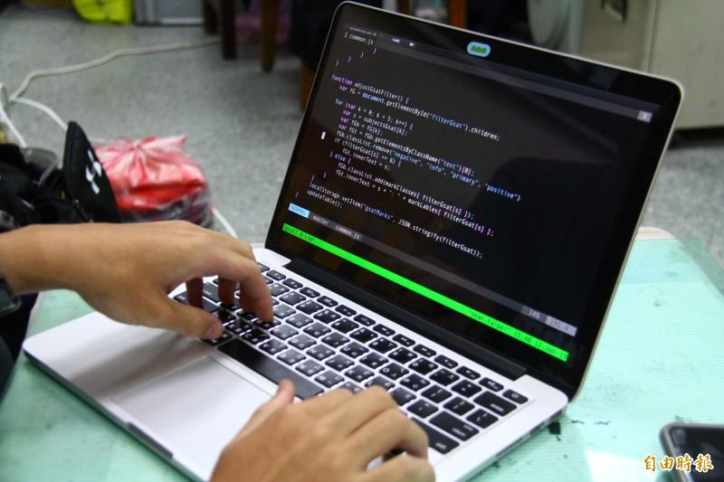韋詠祥敲著鍵盤解釋程式語言。(記者邱書昱攝)
