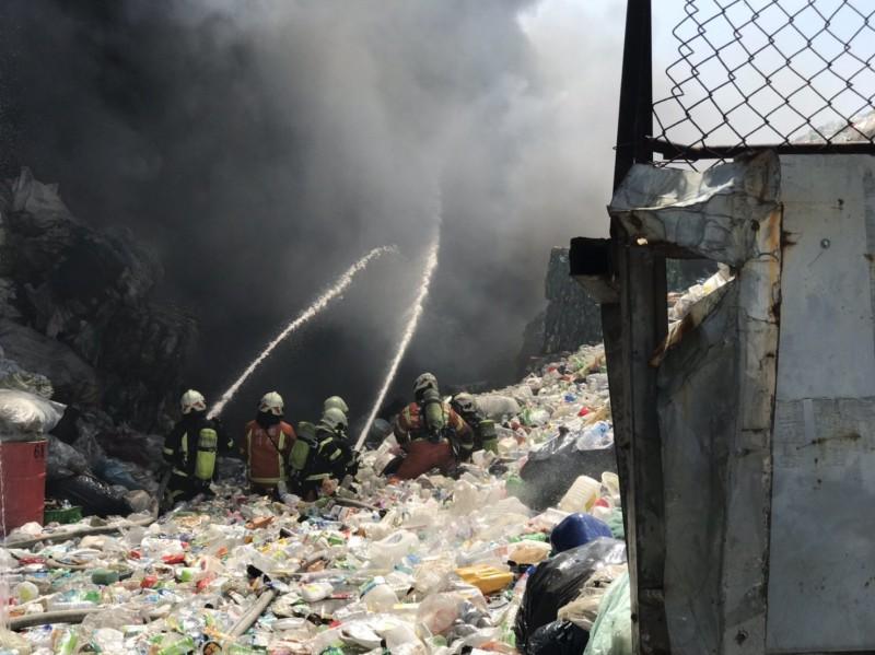 中壢資源回收場大火濃煙竄天,消防人員全力救火。(記者李容萍翻攝)