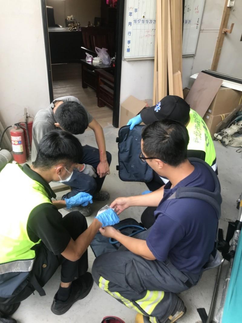 消防人員協助工人包紮送醫。(記者王宣晴翻攝)