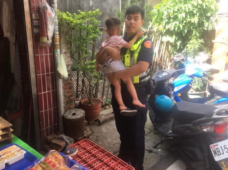 3歲男童市場走失,警尋獲後抱著孩子逐攤詢問。(記者李容萍翻攝)